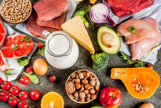 Sfondo di dieta sana ingredienti alimentari biologici supercibi: carne di manzo e maiale carne di maiale filetto di pollo salmone fagioli fagioli noci latte uova frutta verdura tavolo in pietra nera