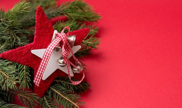 Sfondo di festa con rami di albero di natale decorato con stella rossa su sfondo rosso con uno spazio di copia