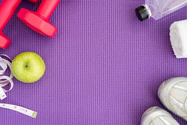 Sfondo di forma fisica con attrezzature su stuoia di yoga