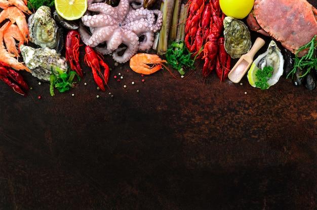 Sfondo di frutti di mare - cozze fresche, molluschi, ostriche, polpi, gusci di rasoio, gamberi, granchi, aragoste, gamberi, alghe, limone, spezie.