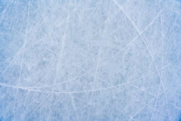 Sfondo di ghiaccio con segni di pattinaggio e hockey, trama blu della superficie della pista con graffi