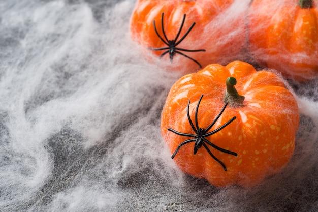 Sfondo di halloween con zucche colorate e ragnatela