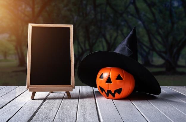 Sfondo di halloween zucca spettrale, lavagna sul pavimento di legno e foresta scura.