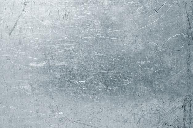 Sfondo di lamiera d'acciaio consumato, struttura in metallo leggero con graffi e ammaccature
