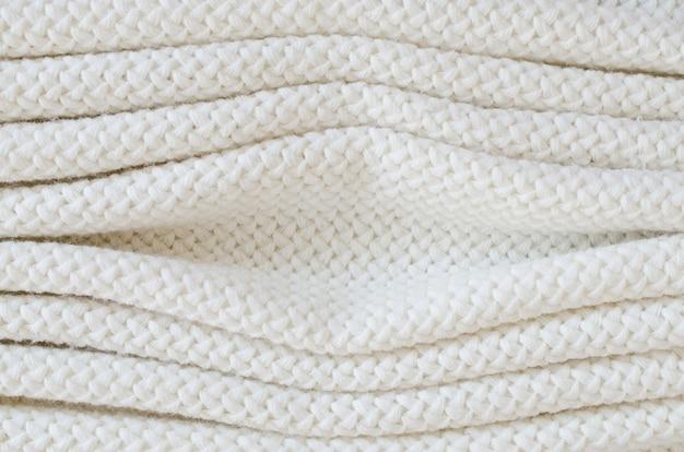 Sfondo di lana a maglia beige. trama del tessuto a maglia.