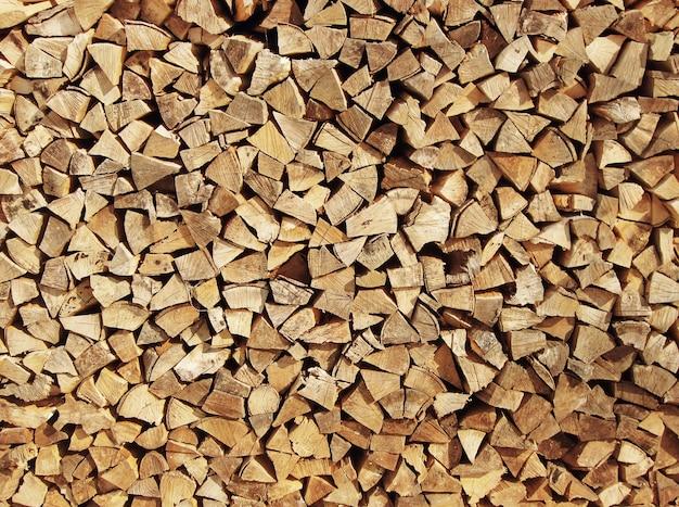 Sfondo di legna da ardere tritata secca registra in un mucchio