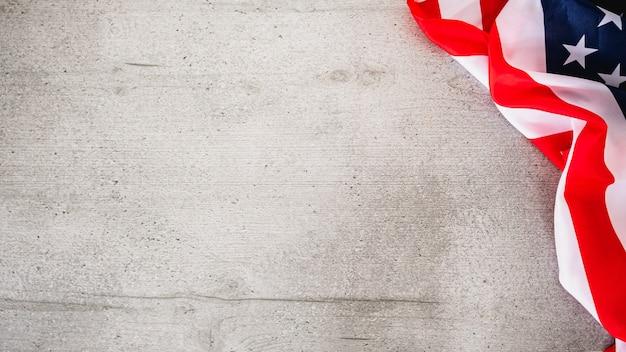 Sfondo di legno grigio con bandiera usa nell'angolo.