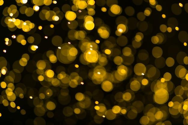Sfondo di luci vintage glitter. oro scuro e nero. defocused