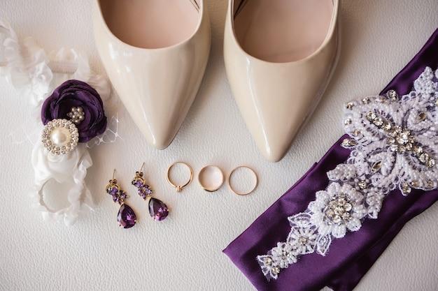 Sfondo di matrimonio. scarpe da sposa, gioielli, giarrettiera e anelli di nozze e proposte su sfondo bianco.