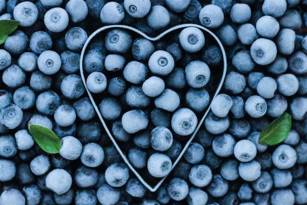 Sfondo di mirtilli freschi congelati a forma di cuore in metallo. texture di mirtilli close-up. la raccolta estiva dei frutti di bosco. spazio per il testo