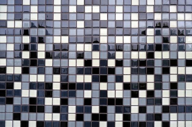 Sfondo di mosaico di piastrelle in ceramica nere, bianche e grigie.