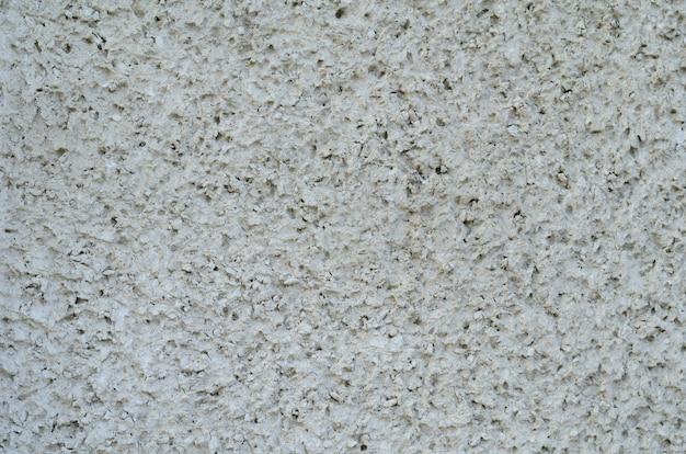 Sfondo di muro di cemento vintage con crepe e fori con molti strati di vernice