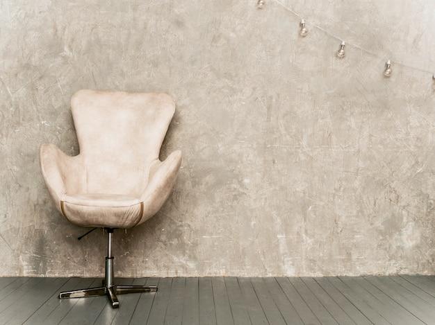 Sfondo di muro grigio interno casa con poltrona in velluto beige e pavimento in legno