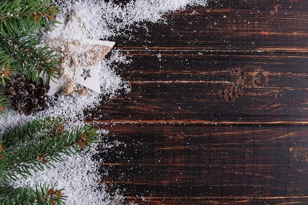 Sfondo di natale, abeti e coni su un tavolo di legno, schiacciato da neve bianca, copia spazio, vista dall'alto.