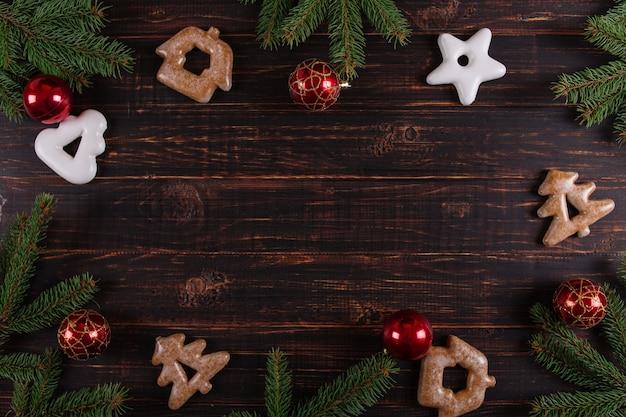Sfondo di natale, alberi di natale, giocattoli e pan di zenzero fatti a mano su un tavolo di legno