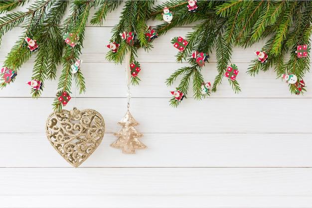 Sfondo di natale. albero di abete di natale, giocattoli dell'albero di natale, cuore dorato e piccolo abete su fondo di legno bianco con lo spazio della copia