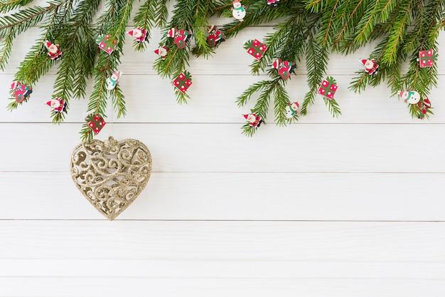 Sfondo di natale. albero di abete di natale, giocattoli dell'albero di natale, cuore dorato su fondo di legno bianco con lo spazio della copia.