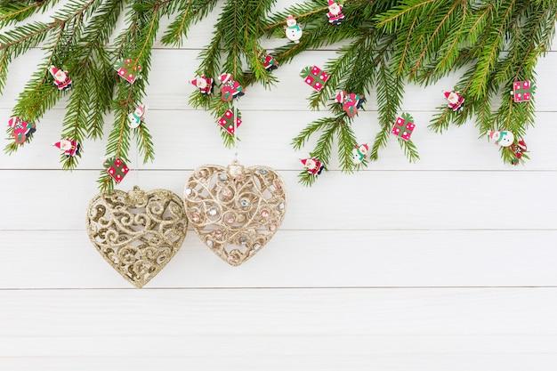 Sfondo di natale. albero di abete di natale, giocattoli dell'albero di natale, due cuori dorati su fondo di legno bianco con lo spazio della copia