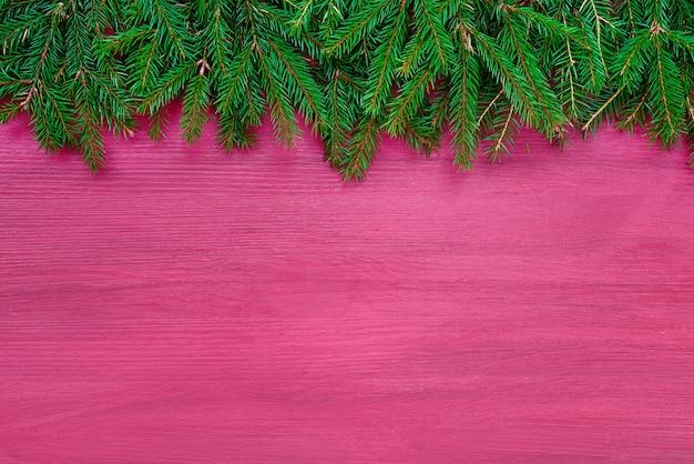 Sfondo di natale. albero di abete di natale su fondo di legno rosa.