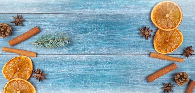 Sfondo di natale: arance secche, stelle di anice, bastoncini di cannella, rametto di abete rosso, su uno sfondo di legno blu