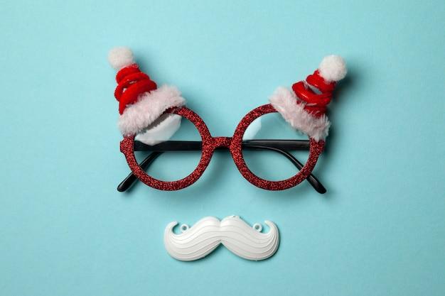 Sfondo di natale blu con occhiali santa e baffi bianchi hipster.