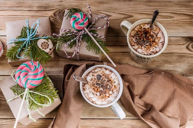 Sfondo di natale. caffè con marshmallow, regali, rami e lecca-lecca su legno