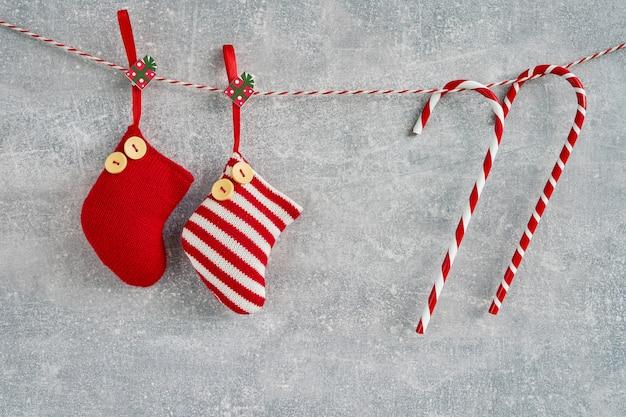 Sfondo di natale. calzini e bastoncini di zucchero rossi di natale su fondo grigio.