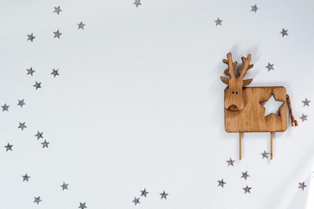 Sfondo di natale. cervo decorativo in legno su stelle. copyspace, vista dall'alto