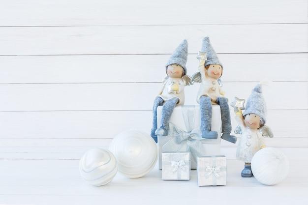 Sfondo di natale. composizione di natale con confezione regalo bianca e gnomi. copia spazio