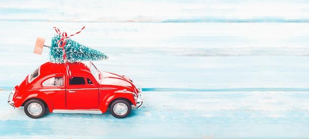 Sfondo di natale con auto rossa e albero di natale