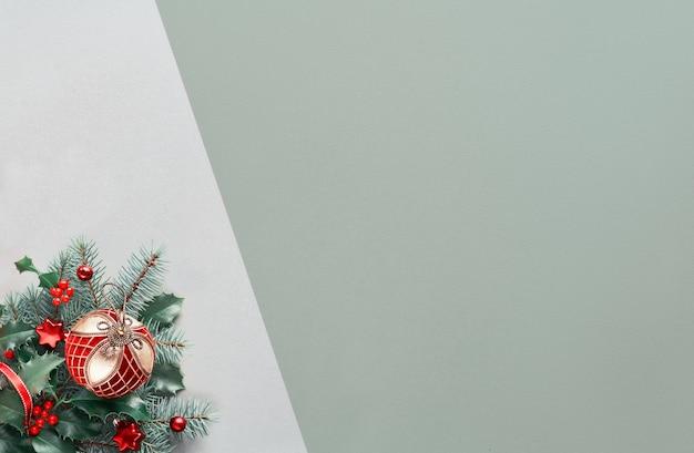 Sfondo di natale con composizione ad angolo - pallina con ornamento d'oro, bastoncini di zucchero a strisce su agrifoglio e ramoscelli di abete. copia-spazio