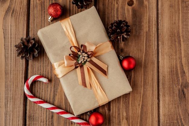 Sfondo di natale con coni di natale e giocattoli, rami di abete, scatole regalo e decorazioni su uno sfondo di tavolo in legno