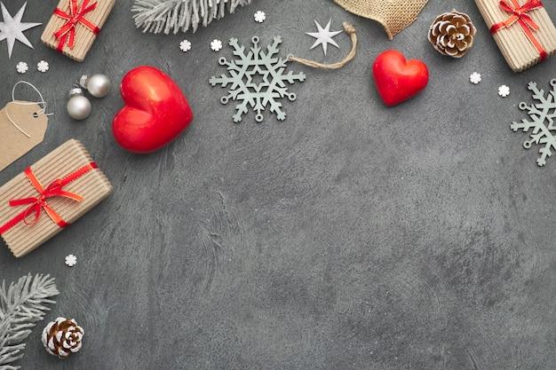 Sfondo di natale con cuori di pietra rossa, regali avvolti, etichette, corde e ninnoli su oscurità
