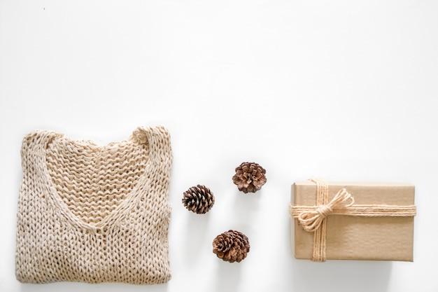 Sfondo di natale con decorazione, regalo, pigne, rami, bolla d'oro e maglione per maglieria e copia spazio