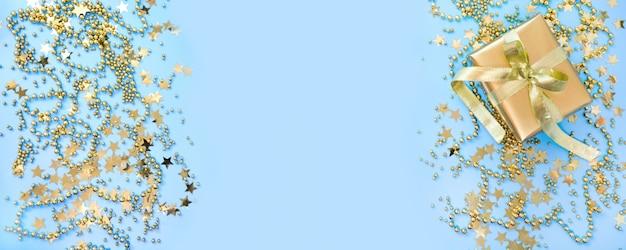 Sfondo di natale con decorazioni dorate di lusso e confezione regalo su blu pastello. disteso. vista dall'alto xmas.