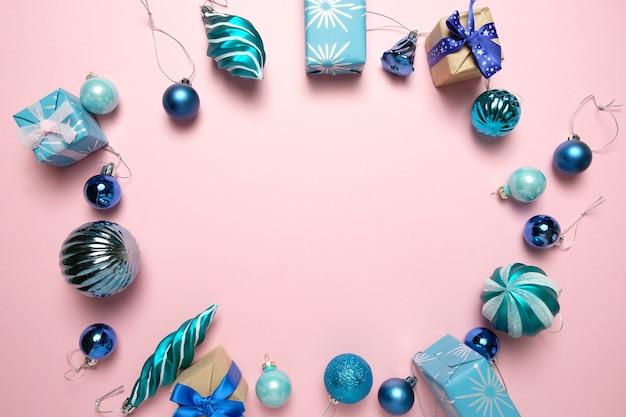 Sfondo di natale con decorazioni e confezioni regalo sul rosa
