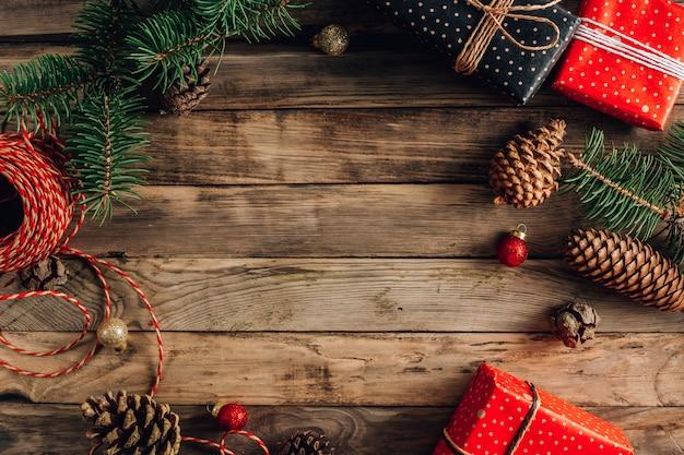 Sfondo di natale con decorazioni e scatole regalo su tavola di legno. vista dall'alto. posto per il testo