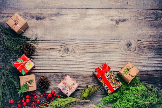 Sfondo di natale con decorazioni e scatole regalo sul bordo di legno.