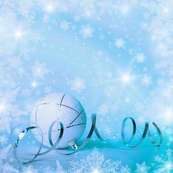 Sfondo di natale con gingillo e fiocchi di neve per auguri