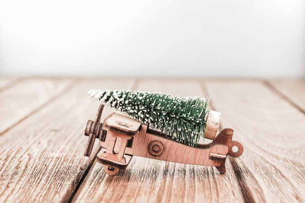 Sfondo di natale con giocattolo aereo in legno vintage con albero di pino in miniatura