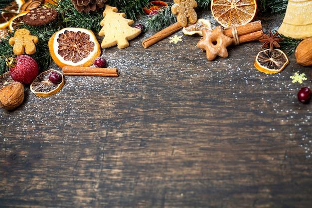 Sfondo di natale con il ramo di un albero di natale, decorazioni festive, frutta secca, biscotti fatti in casa e spezie stagionali tradizionali, vista dall'alto