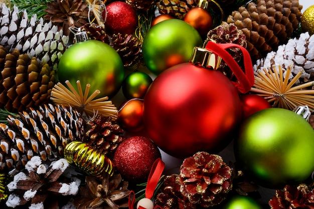 Sfondo di natale con ornamenti rossi, palline verdi e pigne