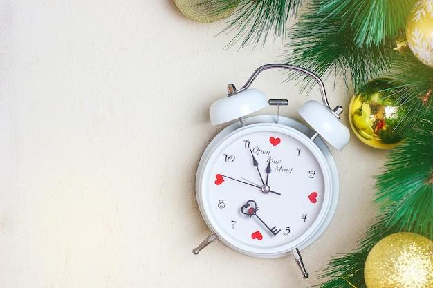 Sfondo di natale con orologio rosso bianco, sfere dorate dell'albero di natale