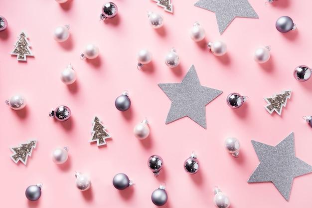 Sfondo di natale con palline d'argento, stelle sul rosa