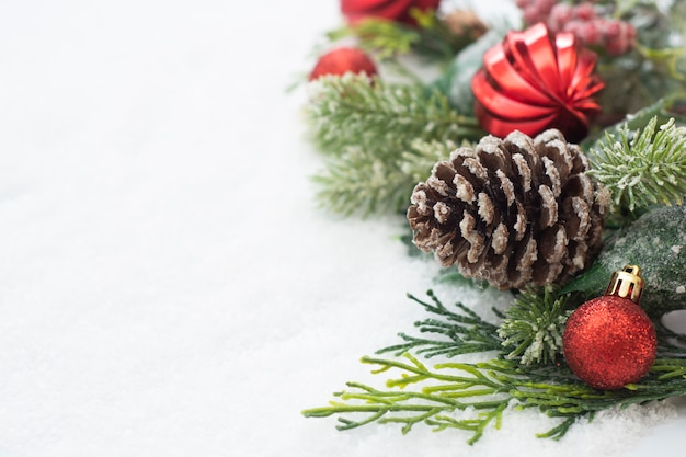 Sfondo di natale con palline, rami di abete verde, pigne, su sfondo bianco neve.