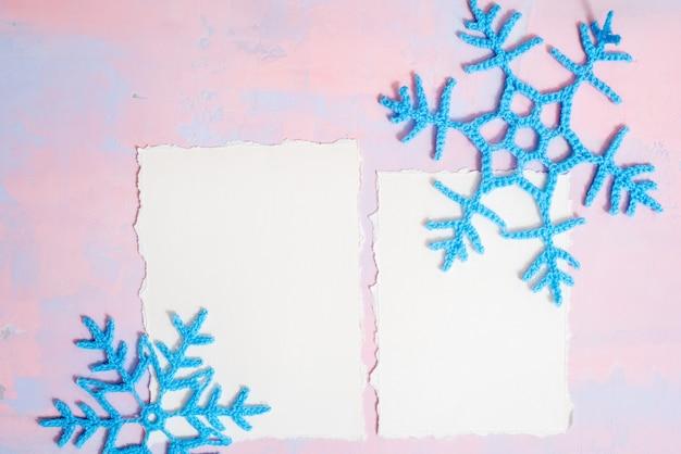Sfondo di natale con quaderno bianco, fiocco di neve all'uncinetto blu, fatto a mano su uno sfondo viola-rosa. tendenza della carta strappata. vista piana, vista dall'alto. copyspace.