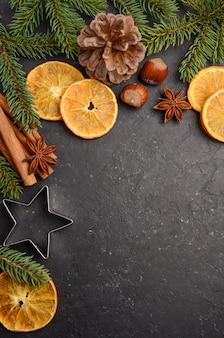 Sfondo di natale con rami di abete, coni, noci e fette di arancia essiccata.