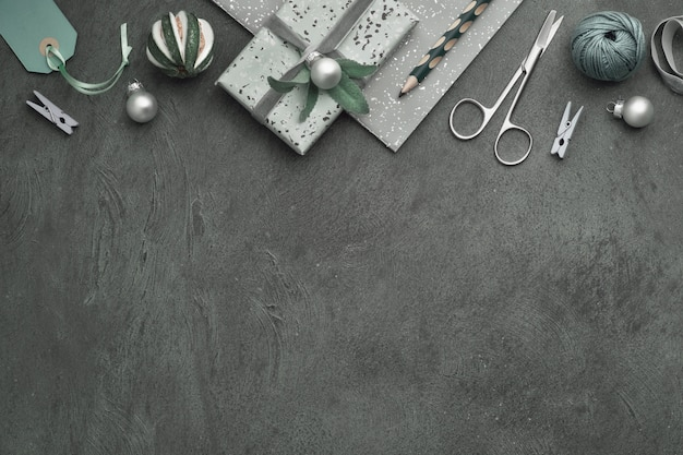 Sfondo di natale con regali avvolti, etichette, corde e ninnoli su sfondo scuro con texture, copia-spazio.