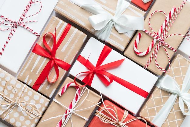 Sfondo di natale con scatole regalo avvolte rosse, artigianali, bianche con nastro colorato e corda, bastoncini di zucchero su sfondo bianco.
