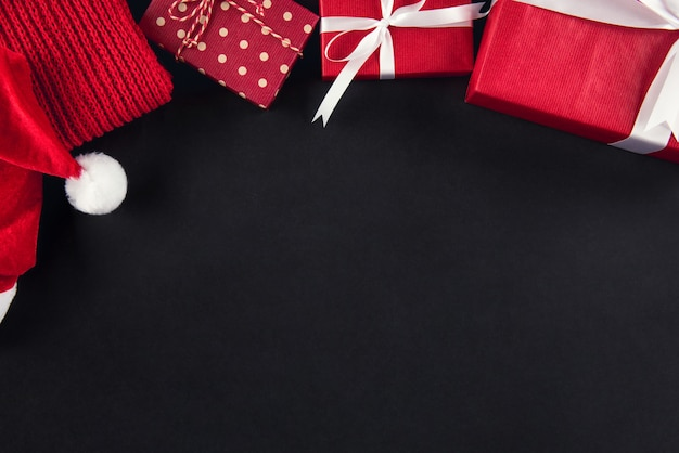 Sfondo di natale con scatole regalo cappello e sciarpa
